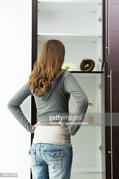 Teen girl standing in front of sparse pantry with hands on hips, rear view