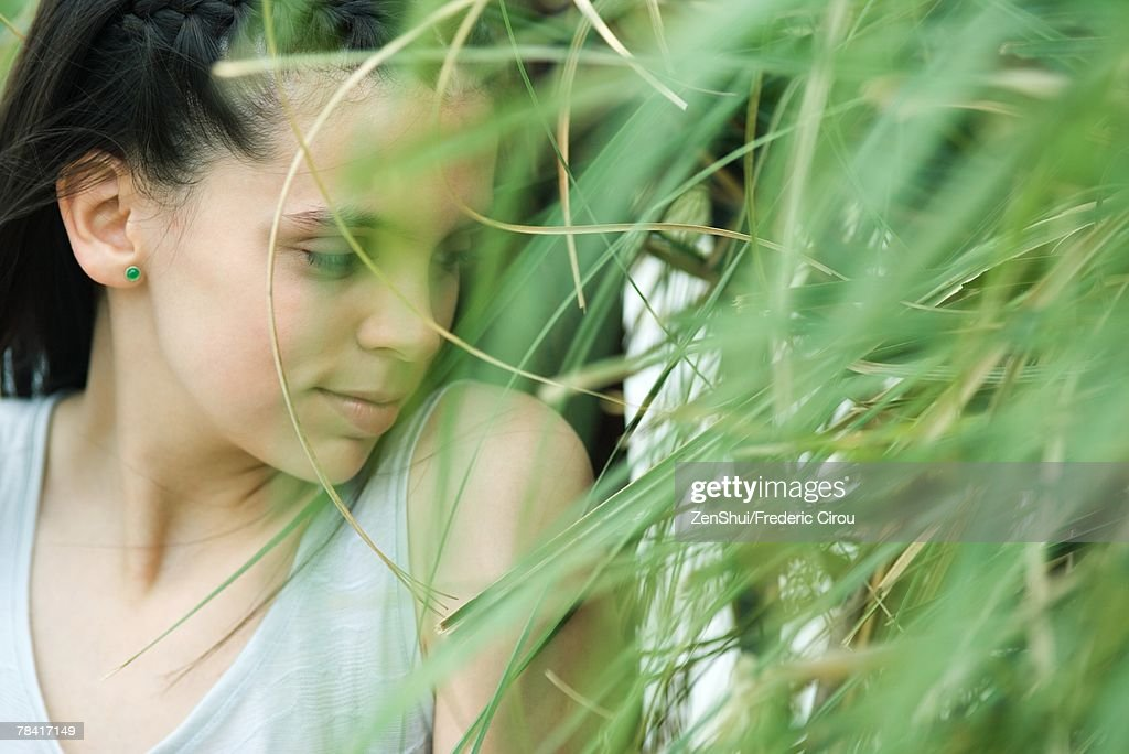 Teen Girl Standing In Thick Foliage Looking Down Stock Photo