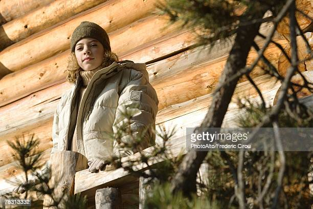 Teen girl standing on deck of log cabin, evergreen in foreground