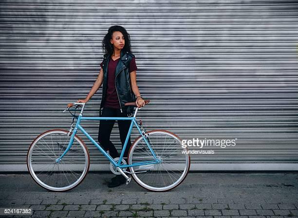 Giovani ragazza in piedi con la bicicletta sulla strada di città