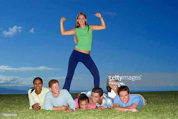 A teen girl stands posing with arms flexed on top of a group of her friends lying in the grass