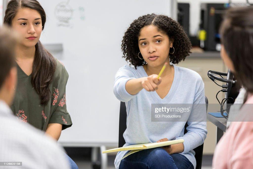 Adolescente leva pergunta durante o grupo de estudo sério colegial : Foto de stock