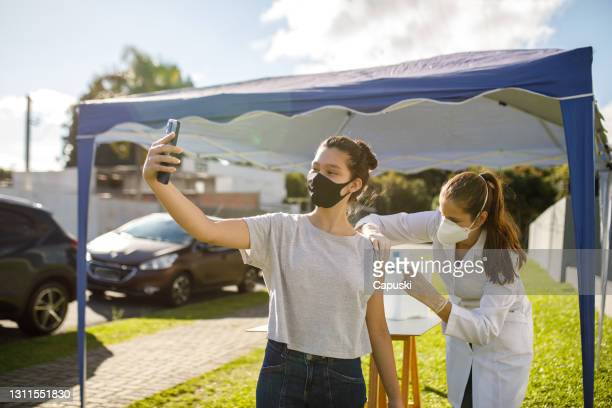 teen girl taking a selfie while taking vaccine - vaccination center stock pictures, royalty-free photos & images