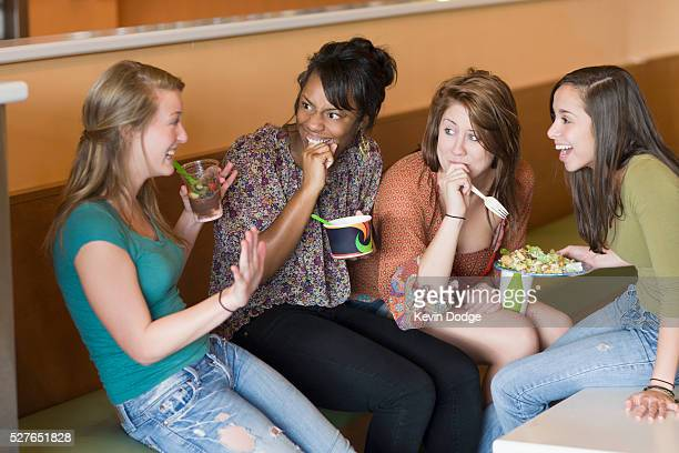 Teen girl telling a story to her friends during lunch