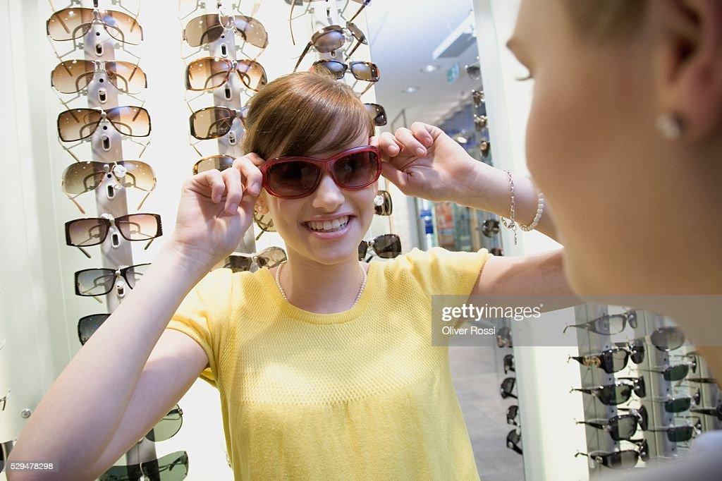 Teen girl trying on sunglasses : Stock Photo