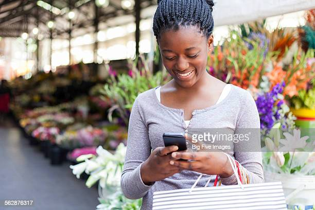 Teen girl using a mobile phone while shopping in a market, Cape Town, Western Cape, South Africa.