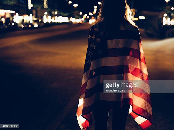 Teen girl walking alone on city street with American flag