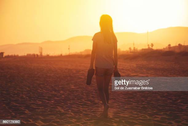 teen girl walking on sand on the beach at sunset - hot high school girls stock photos and pictures