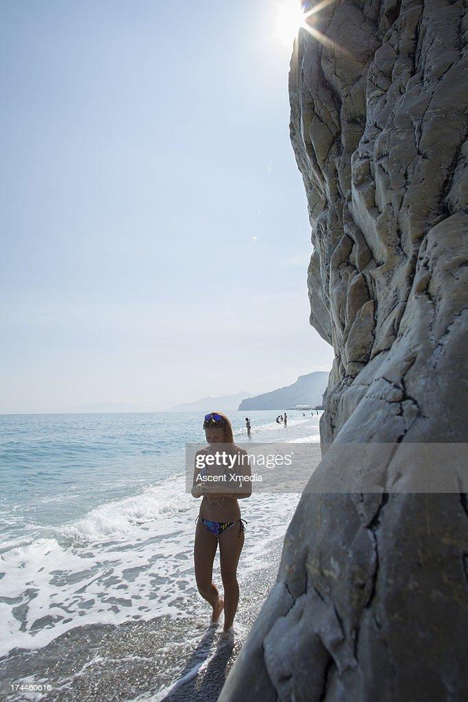 Teen girl walks along beach below cliff, texting : Stock Photo