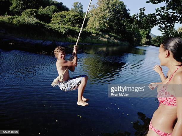 Teen girl watching teen boy (14-16) on rope swing over water, summer