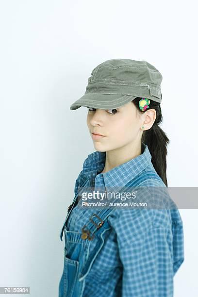 'Teen girl wearing overalls and cap, portrait'