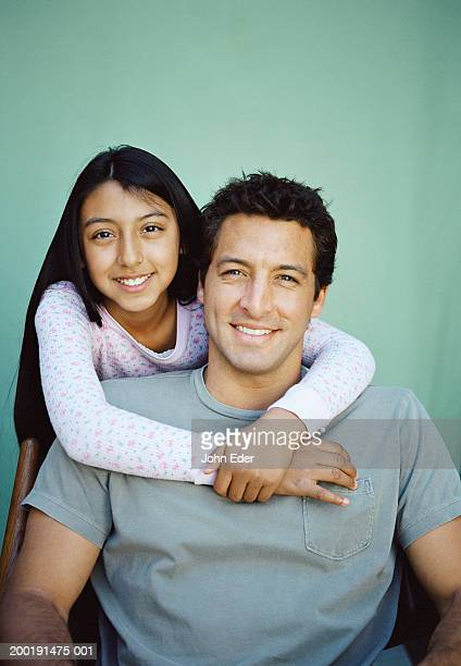 Teen girl (12-14) with arms around father
