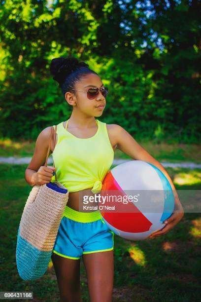 Teen girl with beach ball and sunglasses ready to go to beach