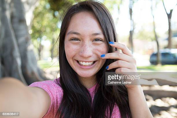 Teen girl with blue nails taking a happy selfie