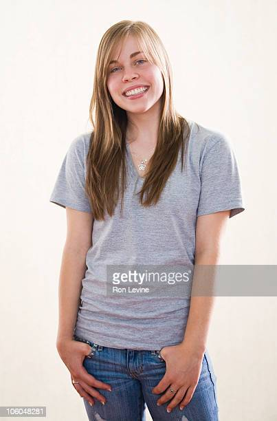 Teen girl with hands in jeans pockets, portrait