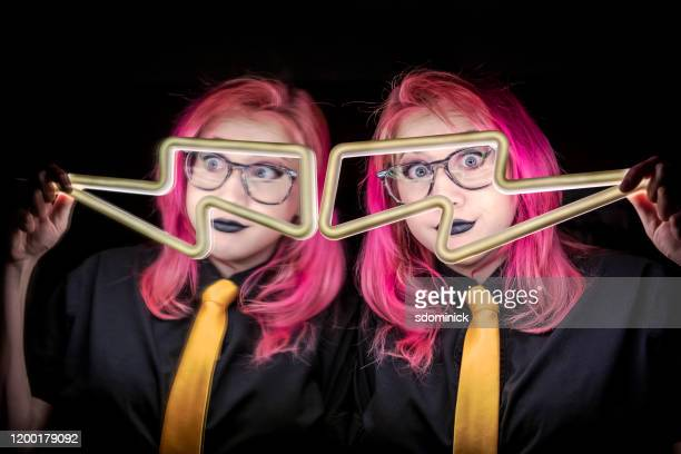teen girl with pink hair looking through lightning bolt light - punk music stock pictures, royalty-free photos & images