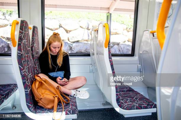 teen girl with red hair tavels on the train listening to music and looking at her mobile phone - public transport stock pictures, royalty-free photos & images