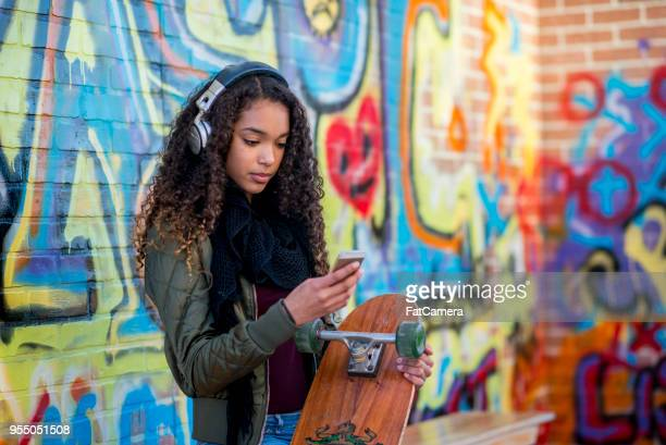 teen girl with skateboard and mp3 stands in front of a graffiti brick wall - sexy teens stock pictures, royalty-free photos & images