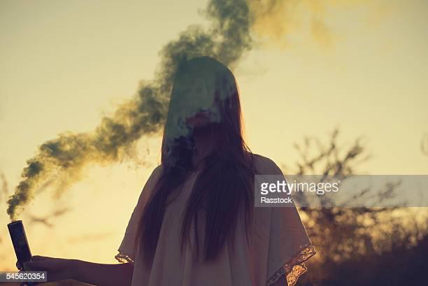 Teen girl with smoke bomb during summertime