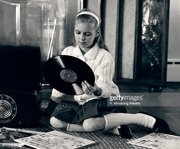 Teen girl with vinyl records and record player, sitting on floor.