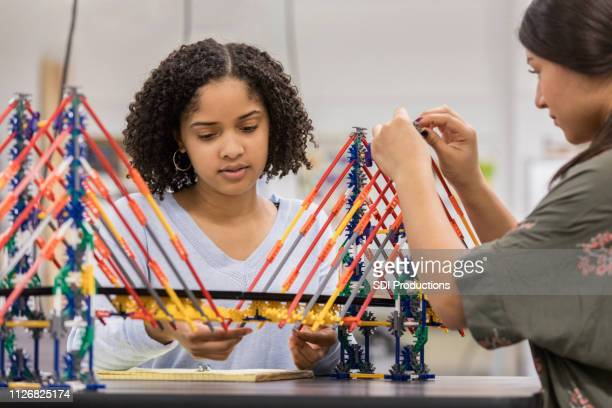 teen girls build bridge at school using model kit - model building stock photos and pictures