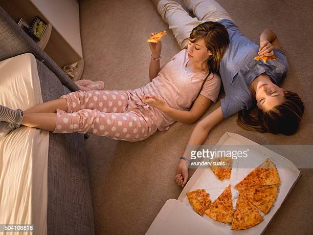 Teen girls eating pizza while lying on a bedroom floor
