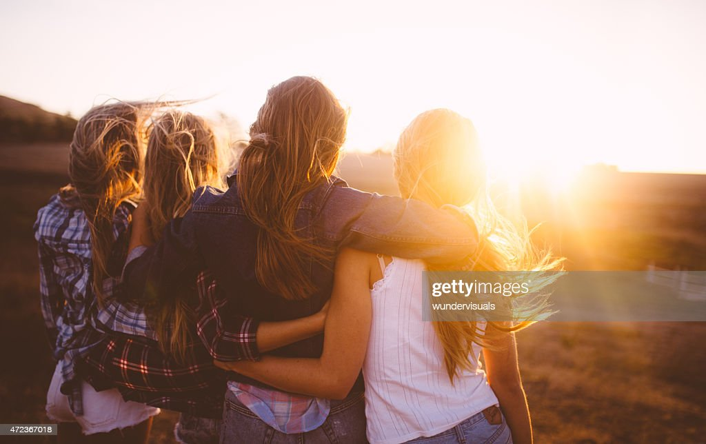 Teen girls facing the sunset with on a summer evening : Stockfoto