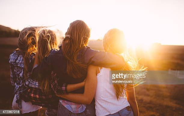 teen girls facing the sunset with on a summer evening - tienermeisjes stockfoto's en -beelden