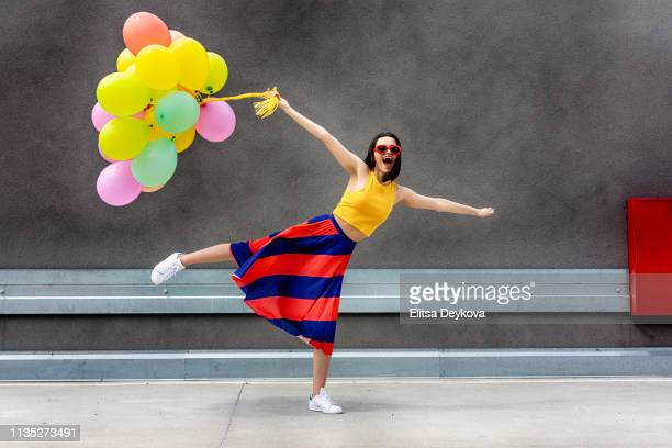 teen girls holding a bunch of balloons - multi coloured dress stock pictures, royalty-free photos & images
