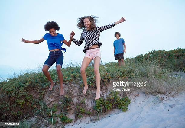 Teen girls jumping from sand dune