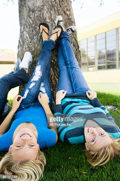 teen girls lay under tree - girl wear jeans and flip flops stock photos and pictures