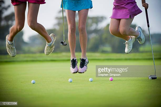 3 teen girls leaping on a putting green