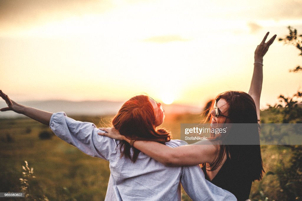 Teen girls look at the sunset : Stock Photo