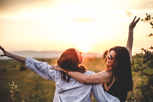 Teen girls look at the sunset 965580802