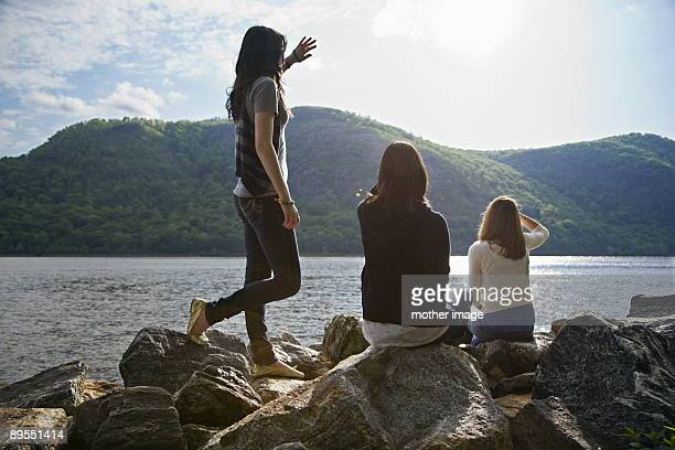 teen girls looking out across lake - westchester county stock pictures, royalty-free photos & images