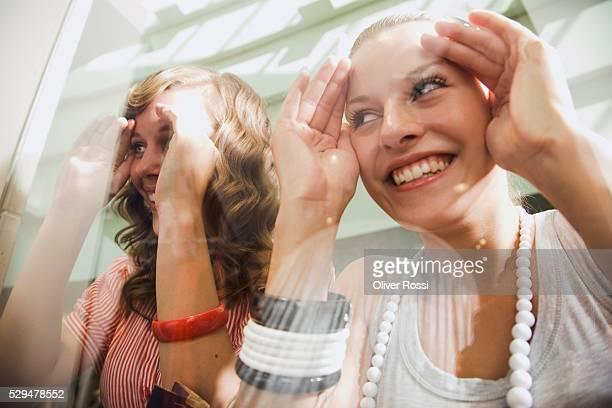 Teen girls looking through shop window