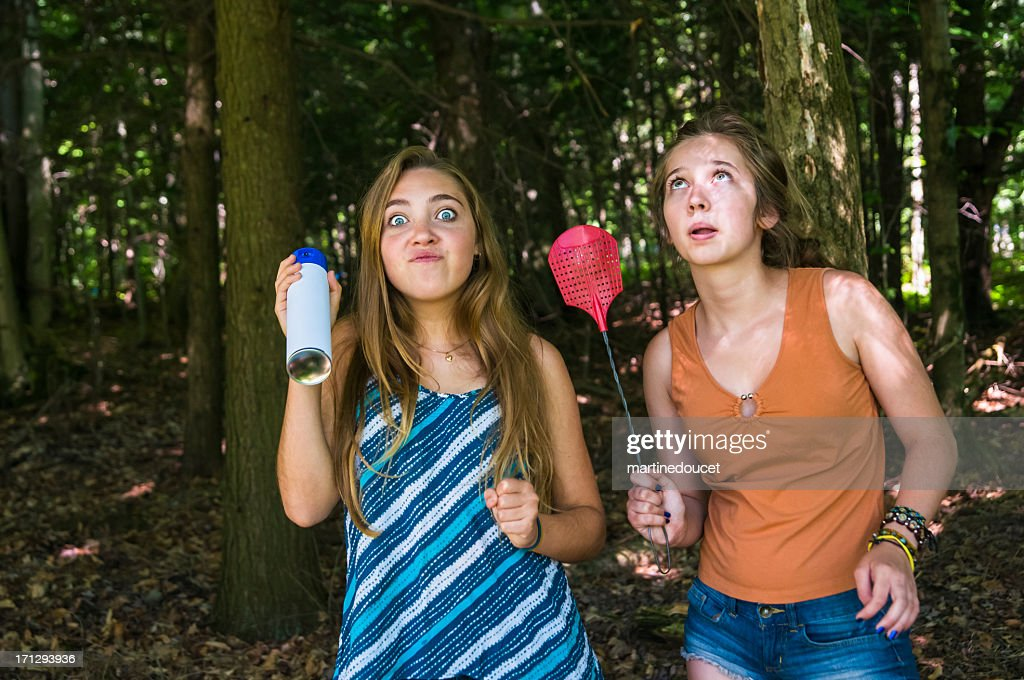 Teen girls make faces chasing insects in a forest : Stock Photo