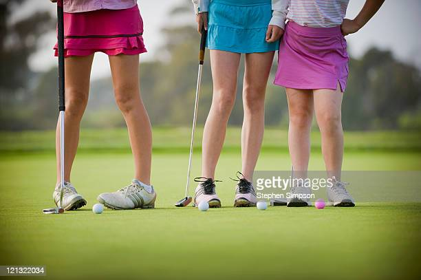 3 teen girls on a golf green, details
