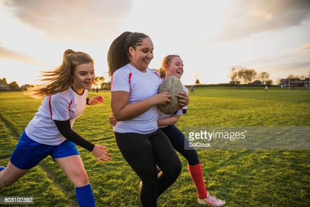 teen girls playing a game of rugby - sporting term stock pictures, royalty-free photos & images