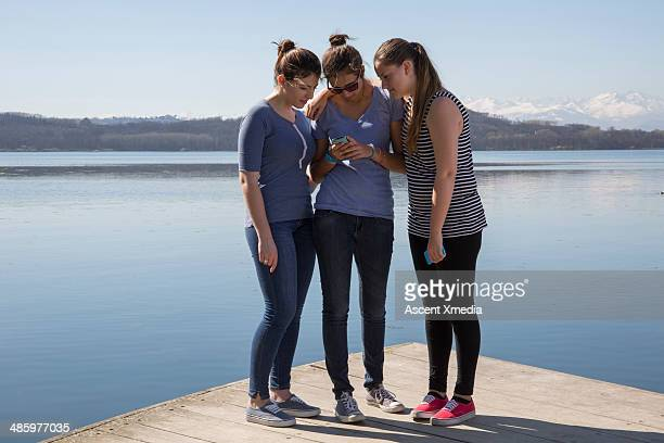 Teen girls share text message on wooden pier, lake