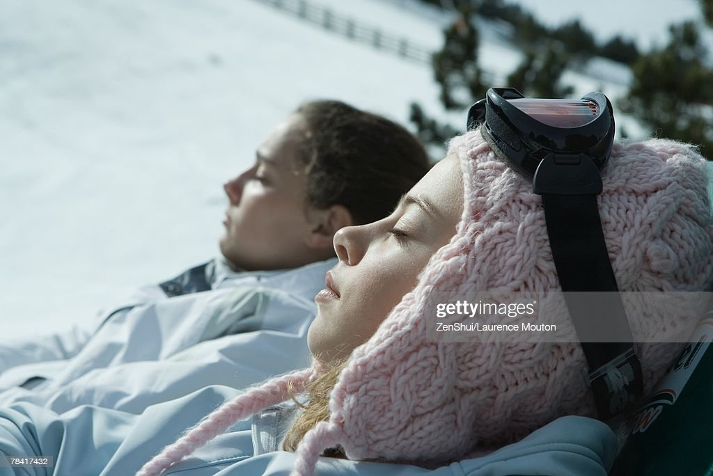 Teen girls sitting in chairs in snowy landscape, relaxing in sun, close-up : Stock Photo