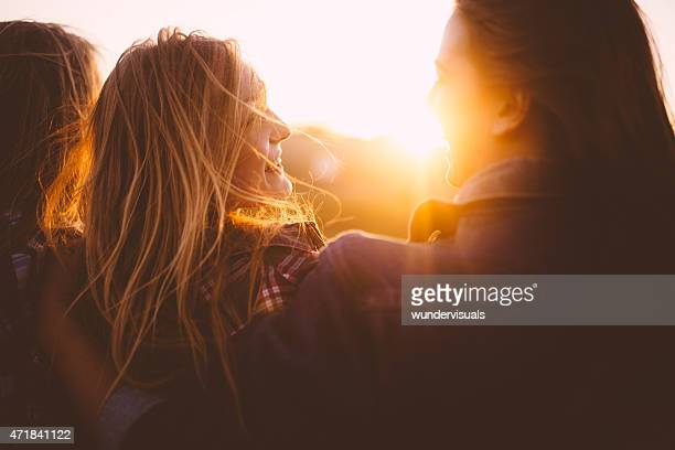Teen girls smiling at each other at sunset