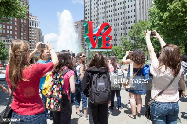 Teen girls take pictures of the 'Love' sculpture in JFK Plaza, Philadelphia