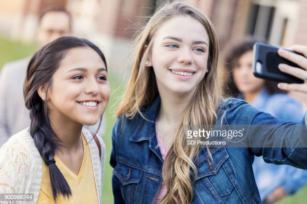 teen girls taking selfie outside on high school campus - camera girls stock photos and pictures