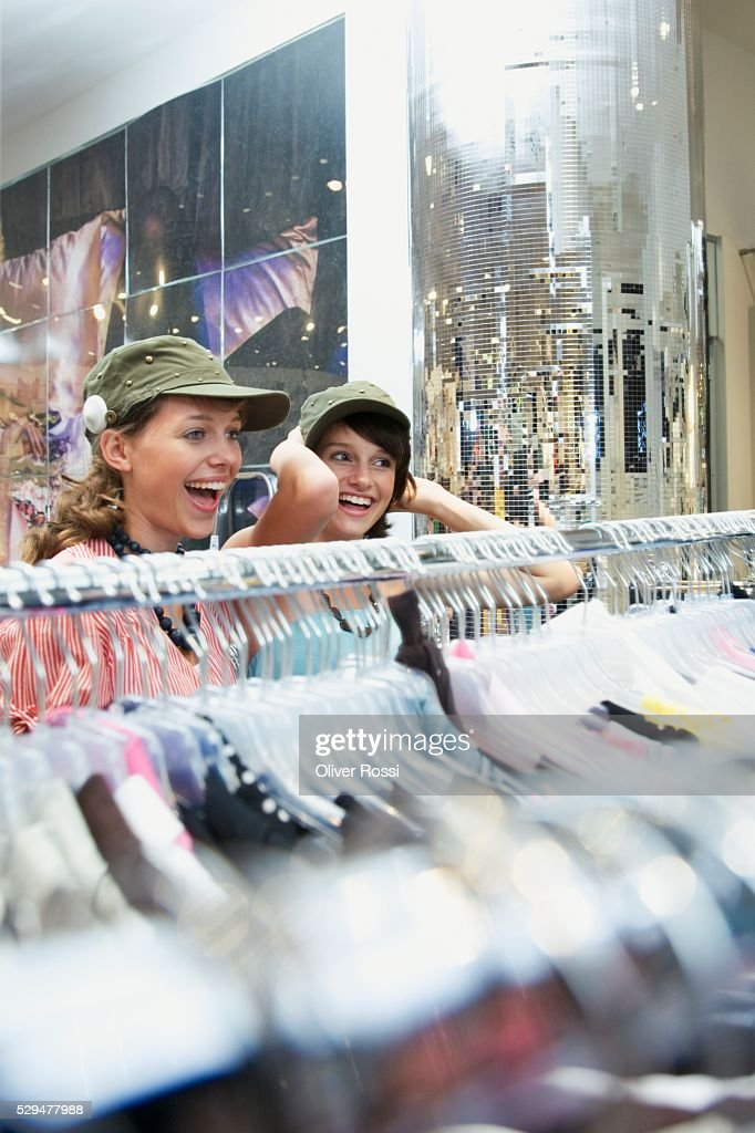 Teen girls trying on caps : Foto de stock