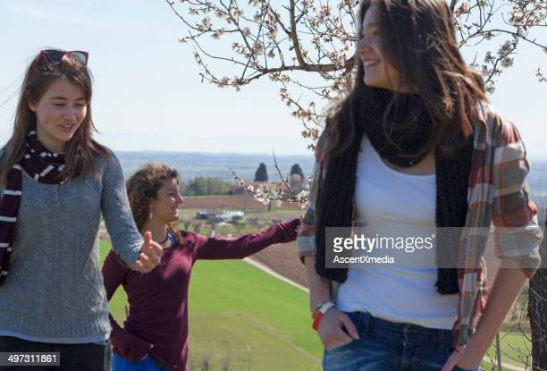 Teen girls walking past blossoms in spring