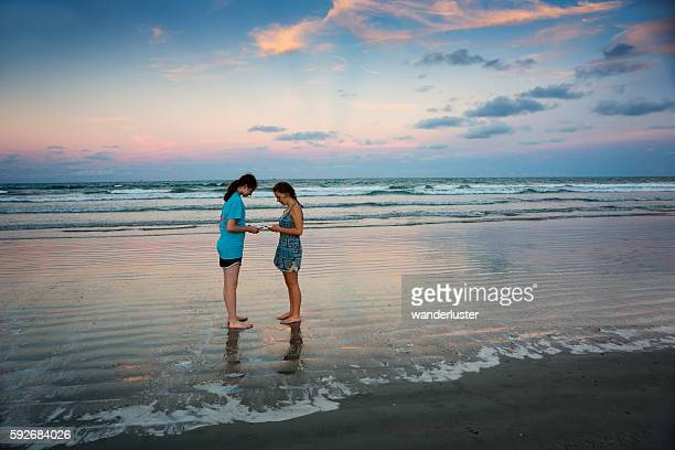 teen girls with smartphones on ocean beach at sunset - cocoa beach stock pictures, royalty-free photos & images
