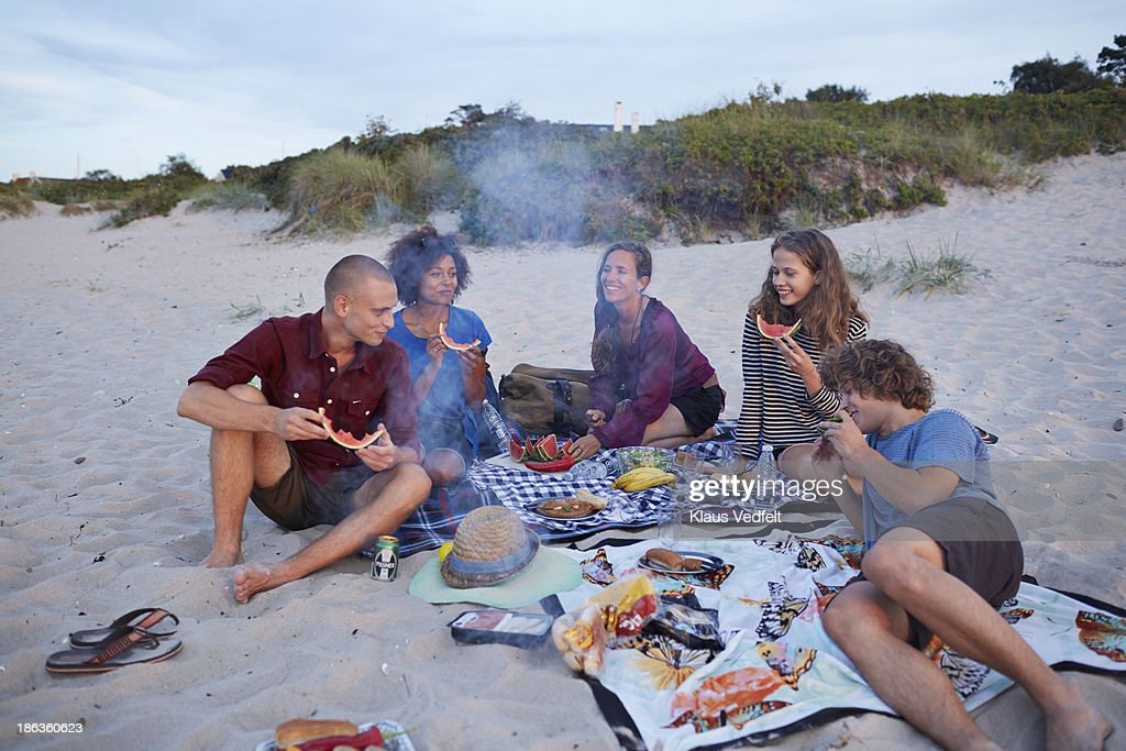Teen group and mother having picnic on beach : Stock Photo