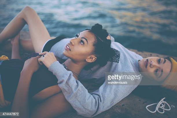 teen grunge girl friends lying together alongside water - dirty little girls photos stock pictures, royalty-free photos & images