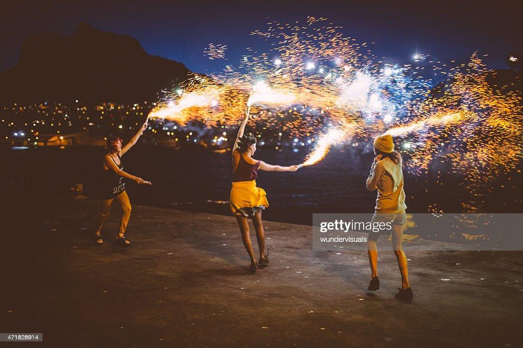 Teen grunge girls dancing with firework flares at night : Stock Photo